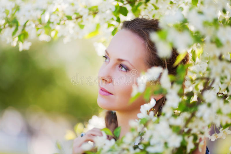 Beautiful fashion woman in a spring garden. Portrait of young beautiful fashion woman among a spring blossom trees stock photo