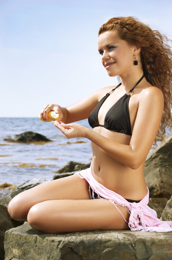 Beautiful woman squeezes out a cream for sunburns. The girl sits on a stone and spreads sunscreen royalty free stock images