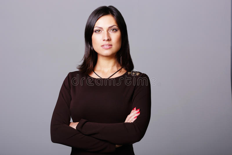 Beautiful woman standing with arms folded. Confident beautiful woman standing with arms folded stock photo