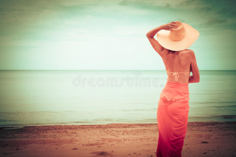 Beautiful woman standing on the beach stock photos