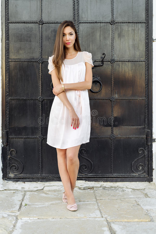 Beautiful woman standing at the black door of the castle, Gothic church . girl in a pink dress, posing close up, resting. Beautiful woman standing at the black stock images