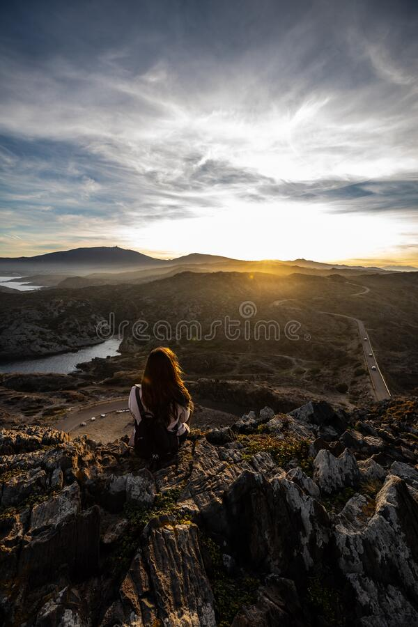 Beautiful woman standing on a cliff during sunset at Cap de Creus, Spain royalty free stock photo