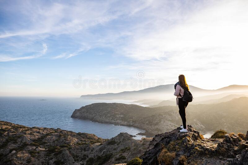 Beautiful woman standing on a cliff during sunset with the mediterranean sea in the background at Cap de Creus royalty free stock images
