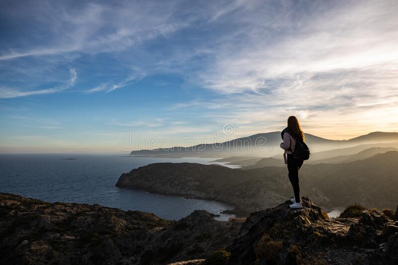 Beautiful woman standing on a cliff during sunset with the mediterranean sea in the background at Cap de Creus stock image