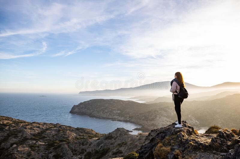 Beautiful woman standing on a cliff during sunset with the mediterranean sea in the background at Cap de Creus stock images