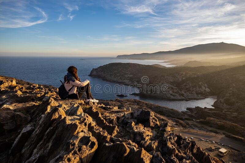 Beautiful woman standing on a cliff during sunset with the mediterranean sea in the background at Cap de Creus stock photography