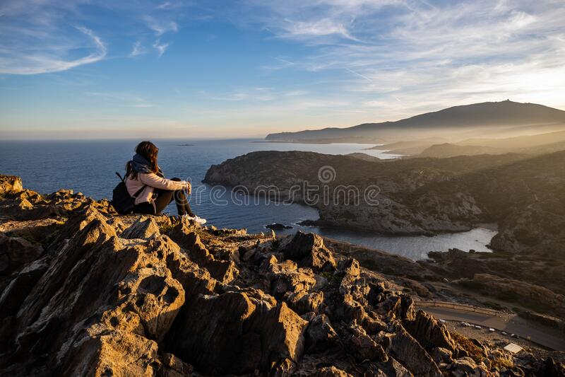 Beautiful woman standing on a cliff during sunset with the mediterranean sea in the background at Cap de Creus royalty free stock photo