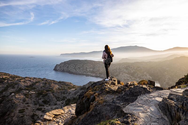 Beautiful woman standing on a cliff during sunset with the mediterranean sea in the background at Cap de Creus stock photo