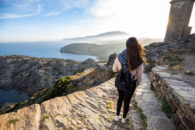 Beautiful woman standing on a cliff during sunset with the mediterranean sea in the background at Cap de Creus royalty free stock image