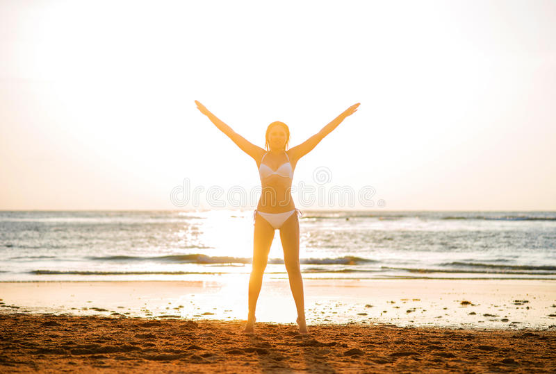 Beautiful woman standing in front of the sunset on the beach.  stock images