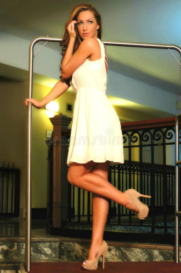 Beautiful Woman Standing on Hotel Luggage Cart. Beautiful woman wearing a white dress & heels brushes hair away from her face as shes standing on a hotel luggage stock photo