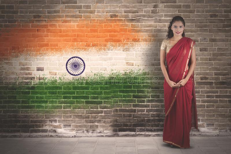 Beautiful woman standing with India flag. Picture of beautiful woman wearing red saree clothes while standing with India flag background royalty free stock photo