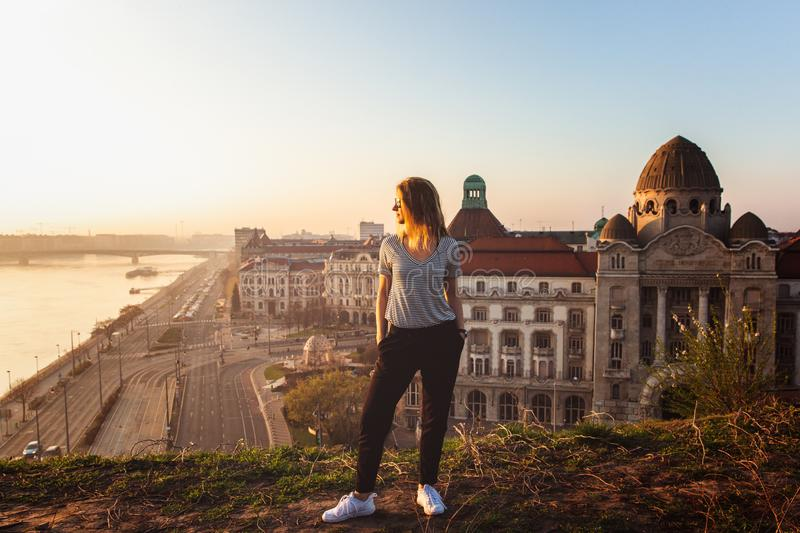Beautiful woman standing opposite famous facade and entrance to Hotel Gellert on banks of Danube in Budapest, Hungary stock image