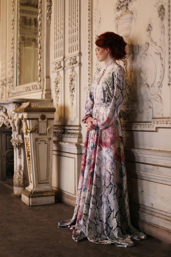 Beautiful woman standing in the palace room. royalty free stock image