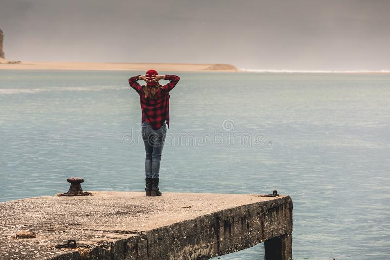 Love my freedom. Beautiful woman standing on a pier with arms raised feeling the freedom royalty free stock images