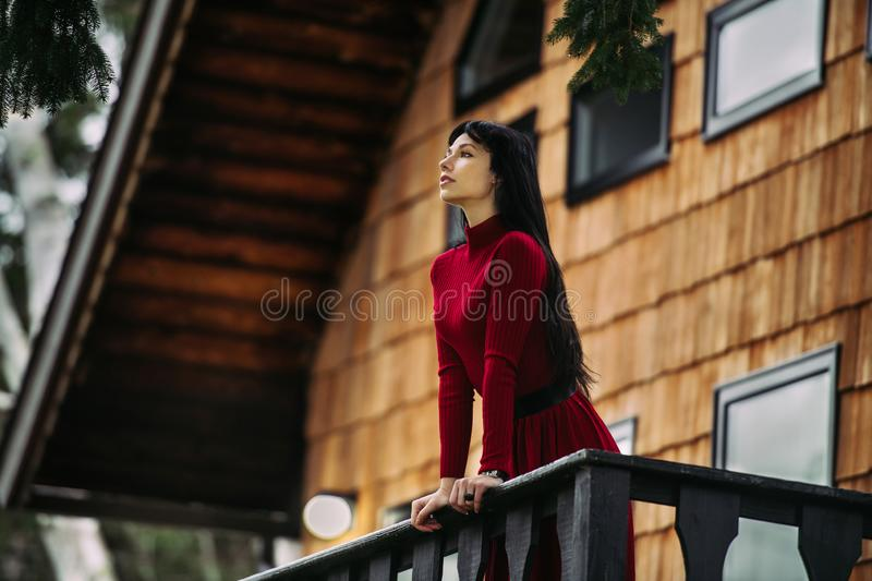 Beautiful woman standing on the porch of wooden house at forest and enjoy the view. stock photo
