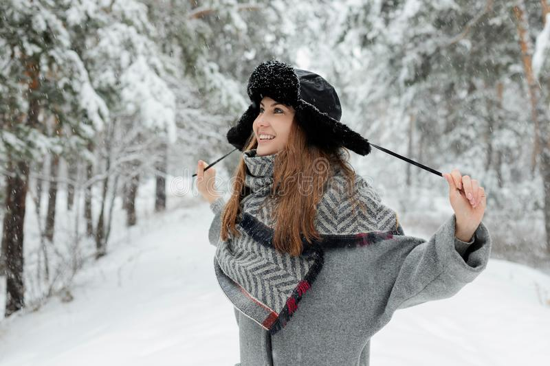 Beautiful young woman standing among snowy trees in winter forest and enjoying snow. royalty free stock photography