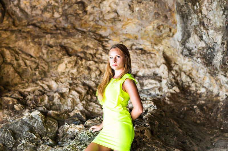 Beautiful woman standing on stones in dark cave. Beautiful woman standing on stones in dark cave royalty free stock image
