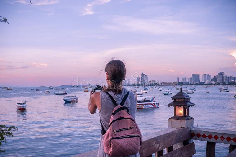 Beautiful woman standing taking a photo of sunset. Happy young woman with a camera and a backpack. Beautiful woman standing taking a photo of sunset. Happy royalty free stock images