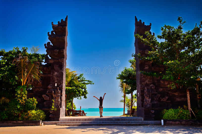 Beautiful woman stands at the entrance Arch Entrance to the Hindu temple. Bali, Indonesia. Beautiful woman stands at the entrance to popular Hindu temple on stock image