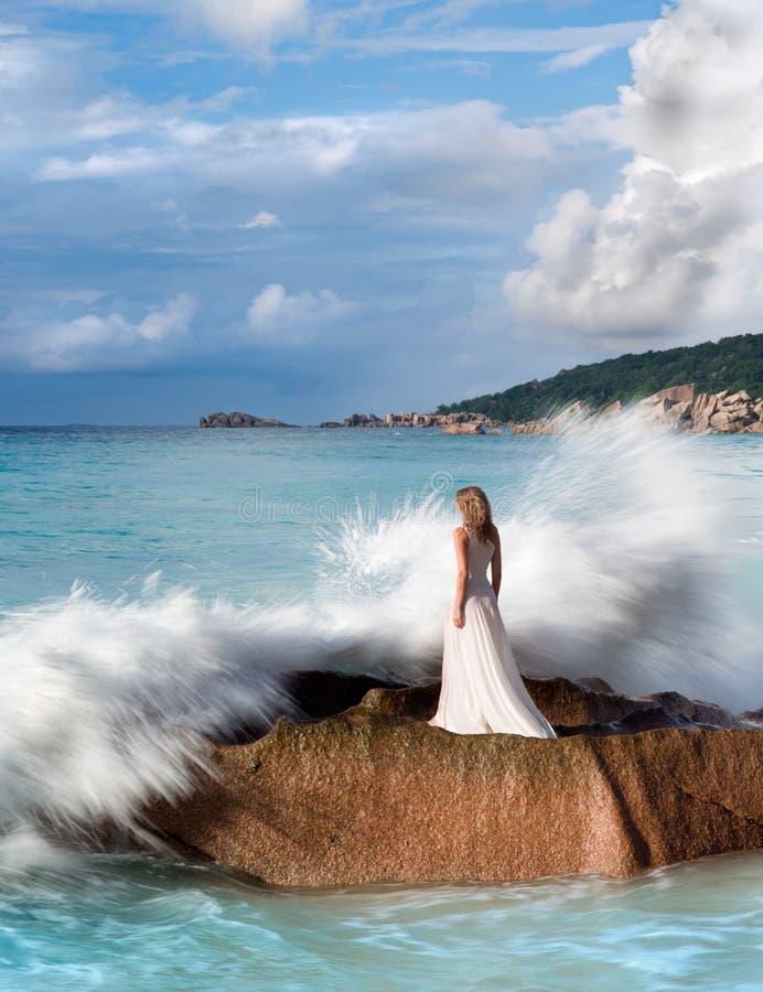 Beautiful woman stands on rock, splashing sea waves, white dress stock photos