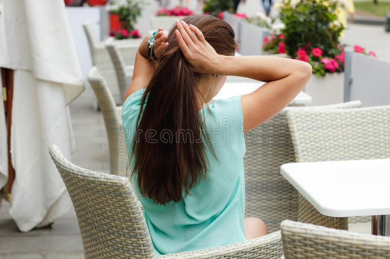 Beautiful woman straightens her hair in a white summer cafe stock images