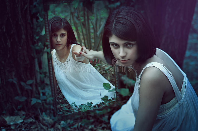 Beautiful woman with a strange mirror royalty free stock images