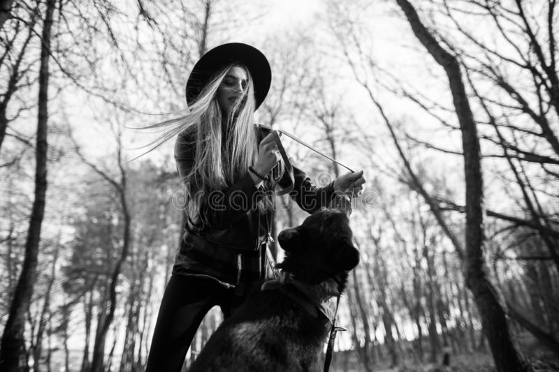 Beautiful woman stroking her dog outdoors. Pretty girl playing and having fun with her pet by name Brovko Vivchar. Black and white royalty free stock images