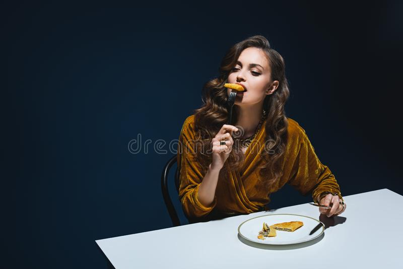 beautiful woman in stylish clothes eating meat pastry at table stock image