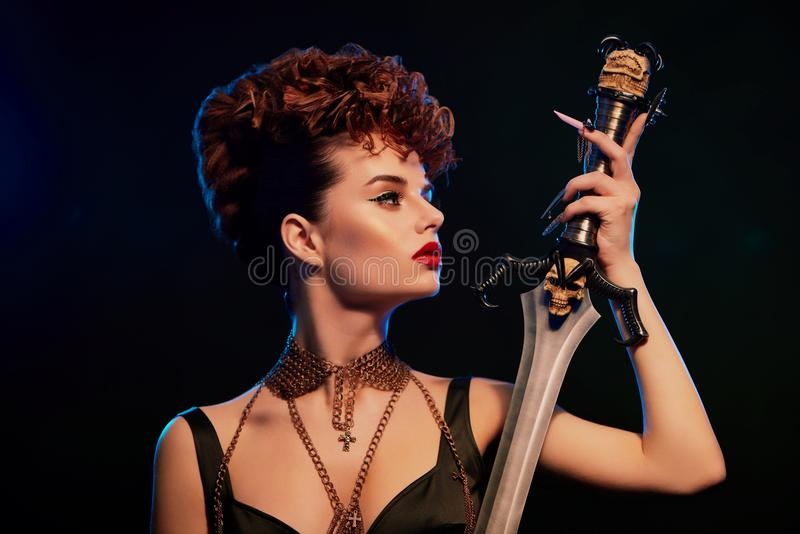 Beautiful woman with stylish hairdress looks on steel sword. Fashionable young model with bright make up keeping steel sword with black skull. Woman wearing royalty free stock photo