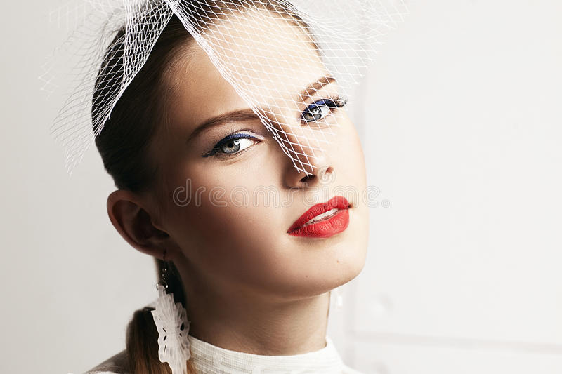 Beautiful woman with stylish hat and elegant white dotted blouse looking forward. royalty free stock image