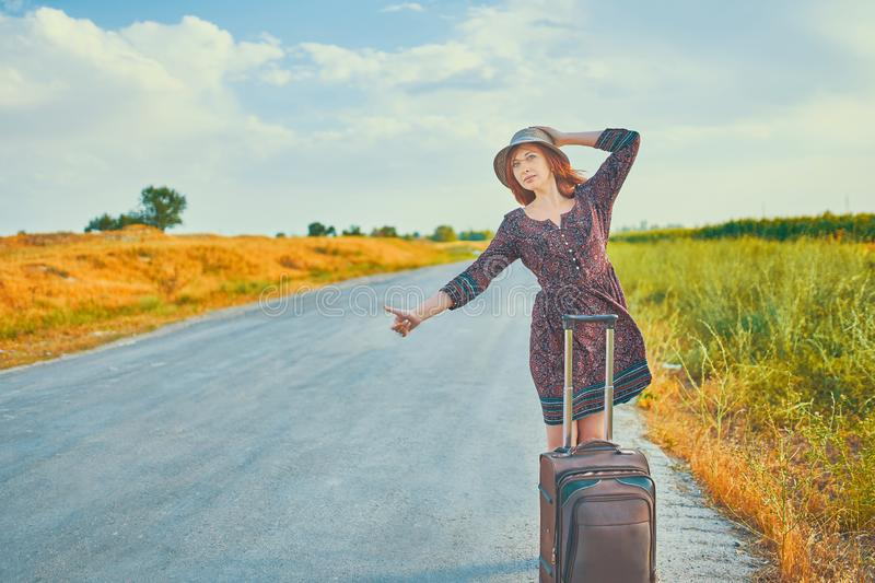 Woman with suitcase thumbs up. Beautiful woman in summer dress and hat hitchhiking with baggage on the road at fall. Cool female hitchhiker thumb up royalty free stock photography
