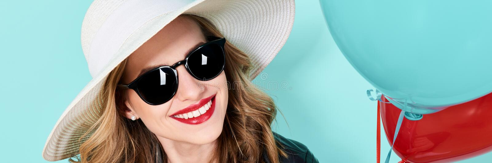 Beautiful woman in summer hat and sunglasses holding balloons. Attractive cool young woman fashion portrait. stock photo