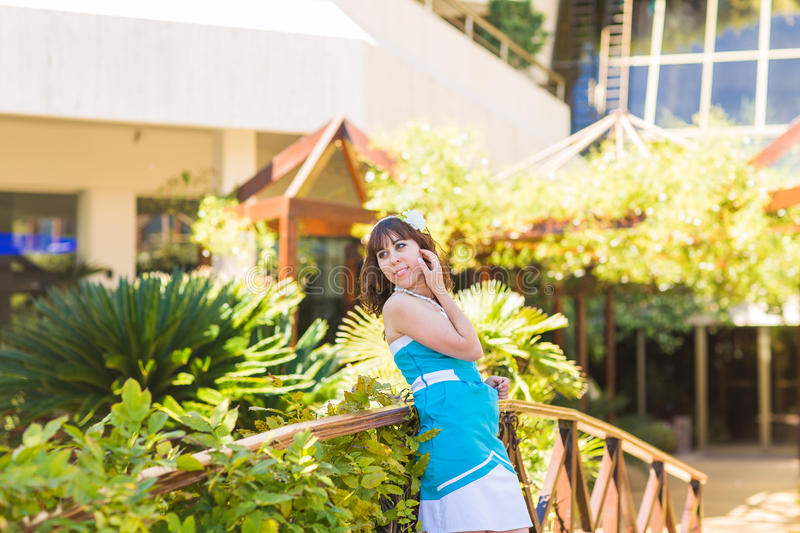 Beautiful woman in summer outfit posing in luxury resort . Holiday vacation mood. Bright blue dress. royalty free stock images