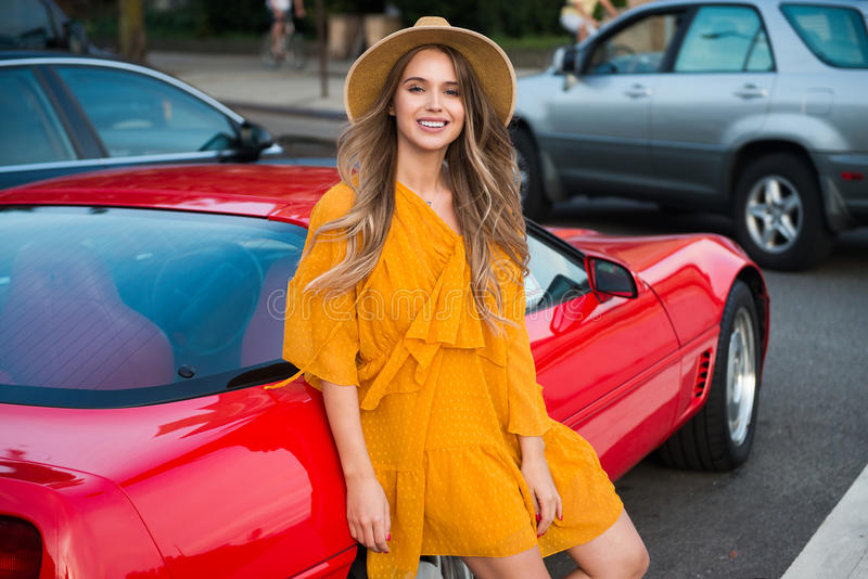 Beautiful woman on summer road trip standing next to her car ready to drive for adventures stock photography
