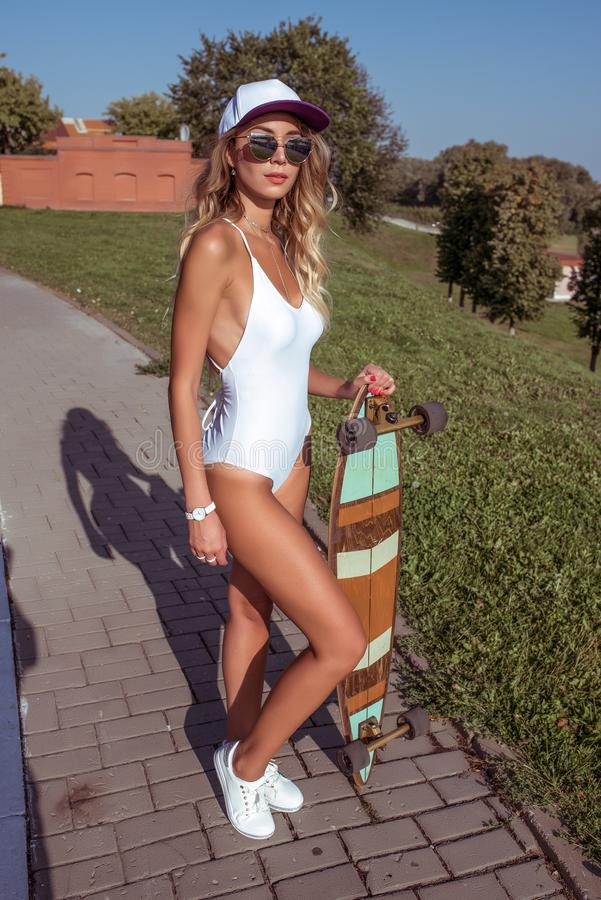 Beautiful woman sunbathes with board, skate longboard. Long hair tanned figure. Concepts fashion youth style, trend and royalty free stock photography