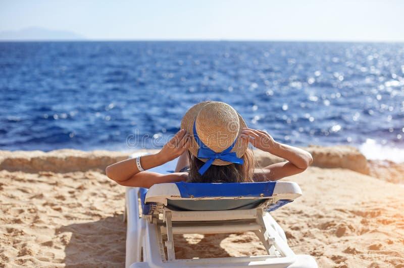 Beautiful woman sunbathing on a beach at tropical travel resort, enjoying summer holidays. Young woman lying on sun royalty free stock image