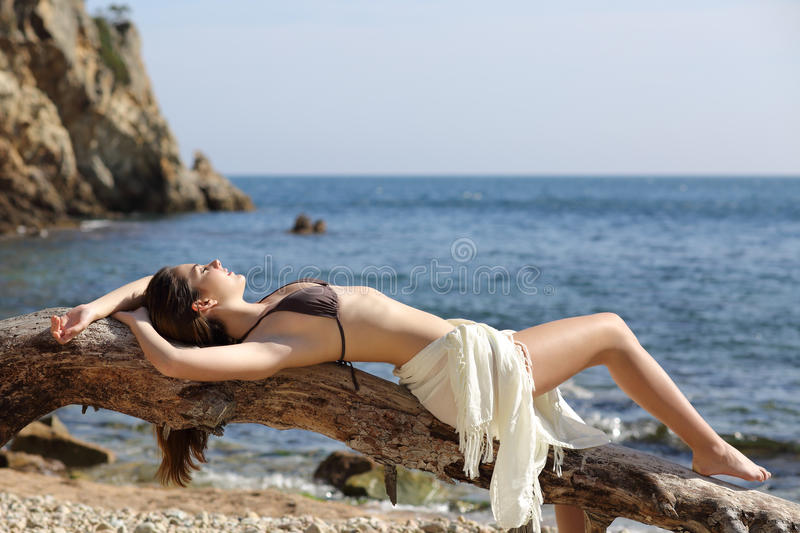 Beautiful woman sunbathing on the beach on vacations stock images