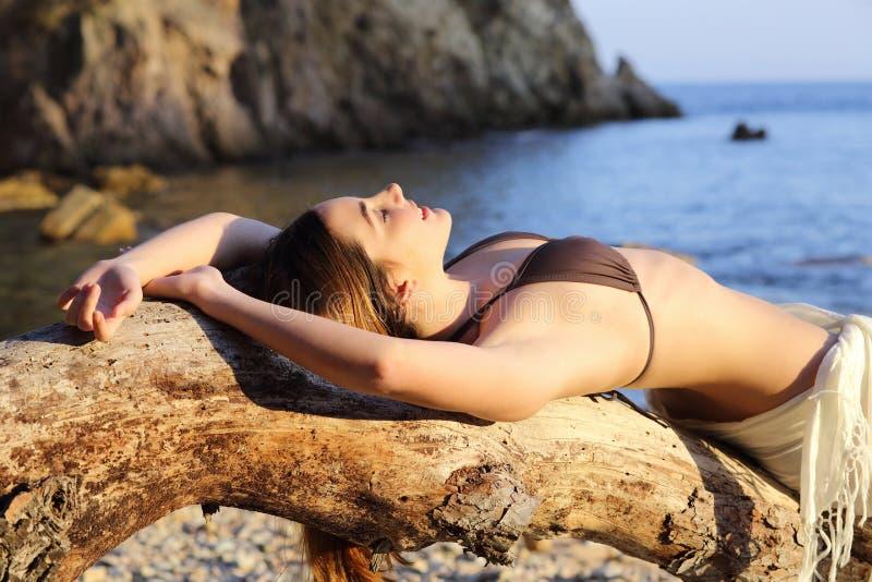Beautiful woman sunbathing on a paradise beach in summer stock photo