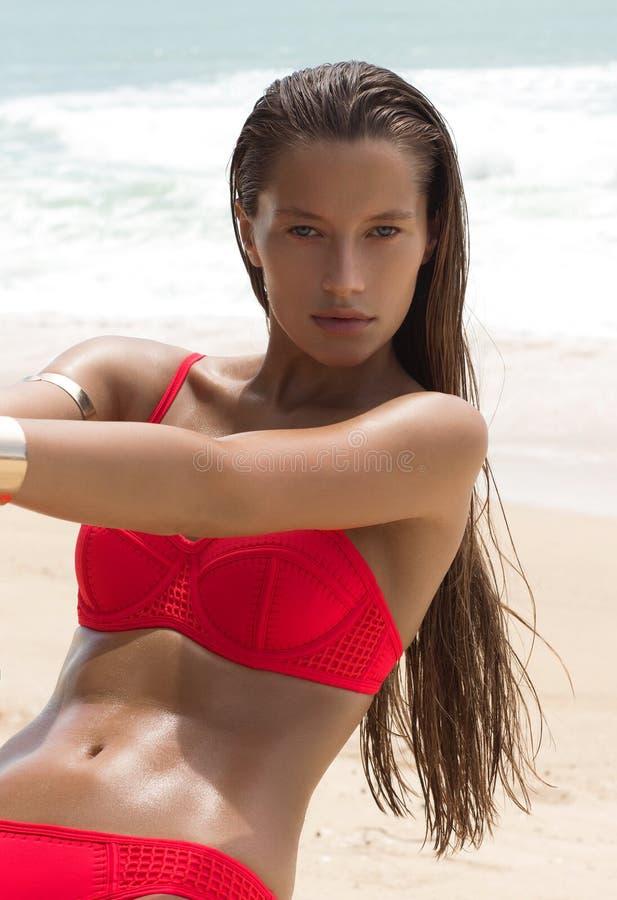Beautiful woman in sunglasses and red bikini on beach. Fashion look. lady royalty free stock image