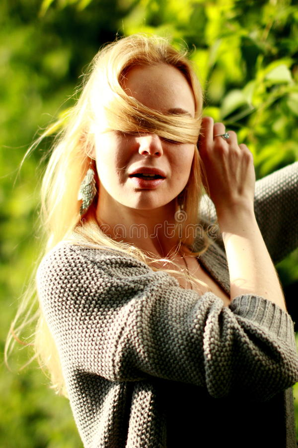 Beautiful woman in the sunny forest, covered her face with hair, fooled. stock photo