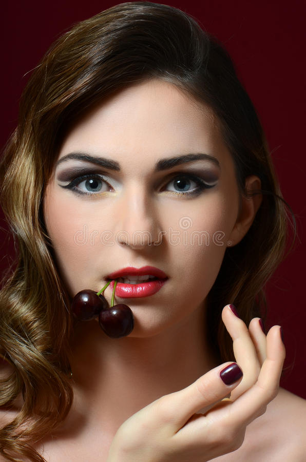 The beautiful woman with sweet cherry stock photo