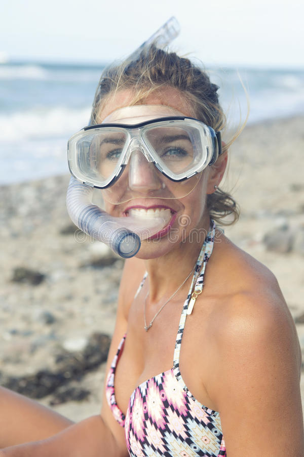 Beautiful woman with swimming goggles on the beach. Portrait of beautiful blond woman with swimming goggles on the beach stock photo