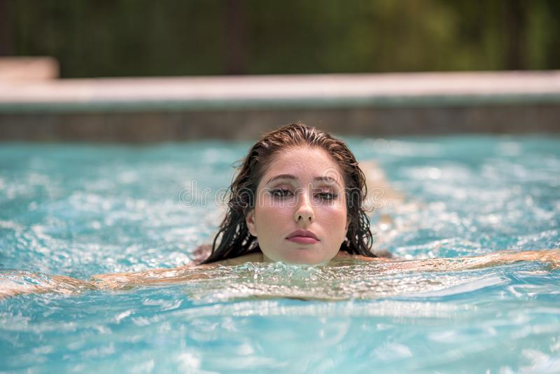 Beautiful woman swimming in a pool blurry background royalty free stock image