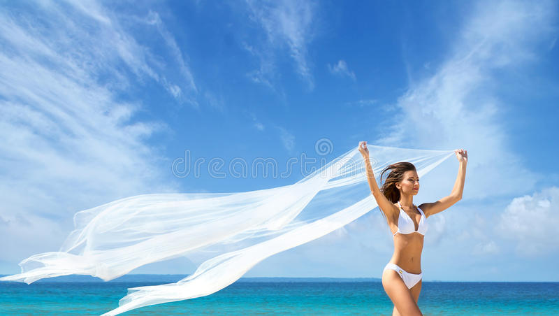A beautiful woman in a swimsuit posing on sky background stock photos