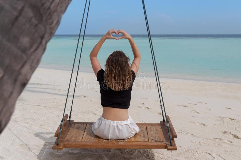 Beautiful woman on a swing attached to a palm frames hand into heart shape, finger heart frame. Crystal clear water of Maldives as royalty free stock images