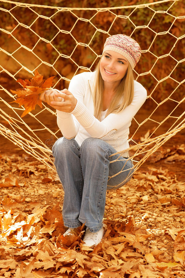 Beautiful woman swinging in hammock. Picture of beautiful woman swinging in hammock, cute smiling girl holding brown autumnal leaves in hands, pretty female royalty free stock photo