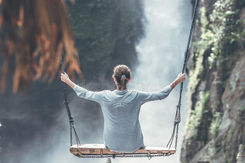 Beautiful woman swings near waterfall in the jungle of Bali island, Indonesia. royalty free stock images