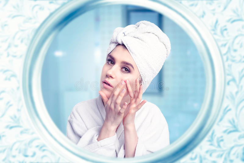 Beautiful woman take care of face against mirror stock images