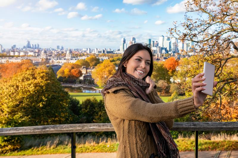 Woman takes selfie photos during autumn time at Greenwich Park in London, UK stock photos